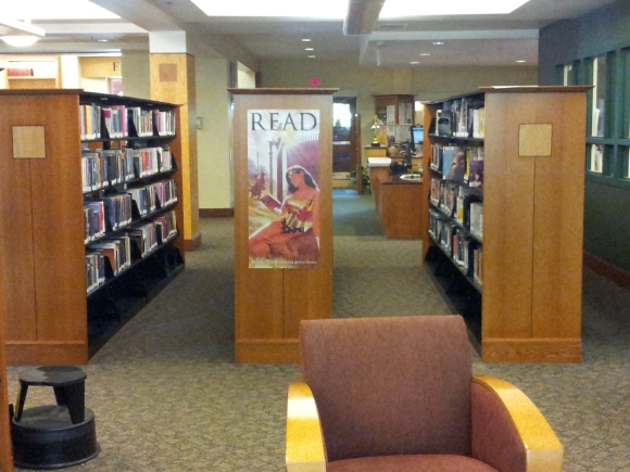 "Looking at my three YA shelves and out to the entrance. The circulation/reader's services department aka ""The Main Desk"" is to the right. I love how convienient the YA area is to both the door and the check out. Gets in them and taking out books."